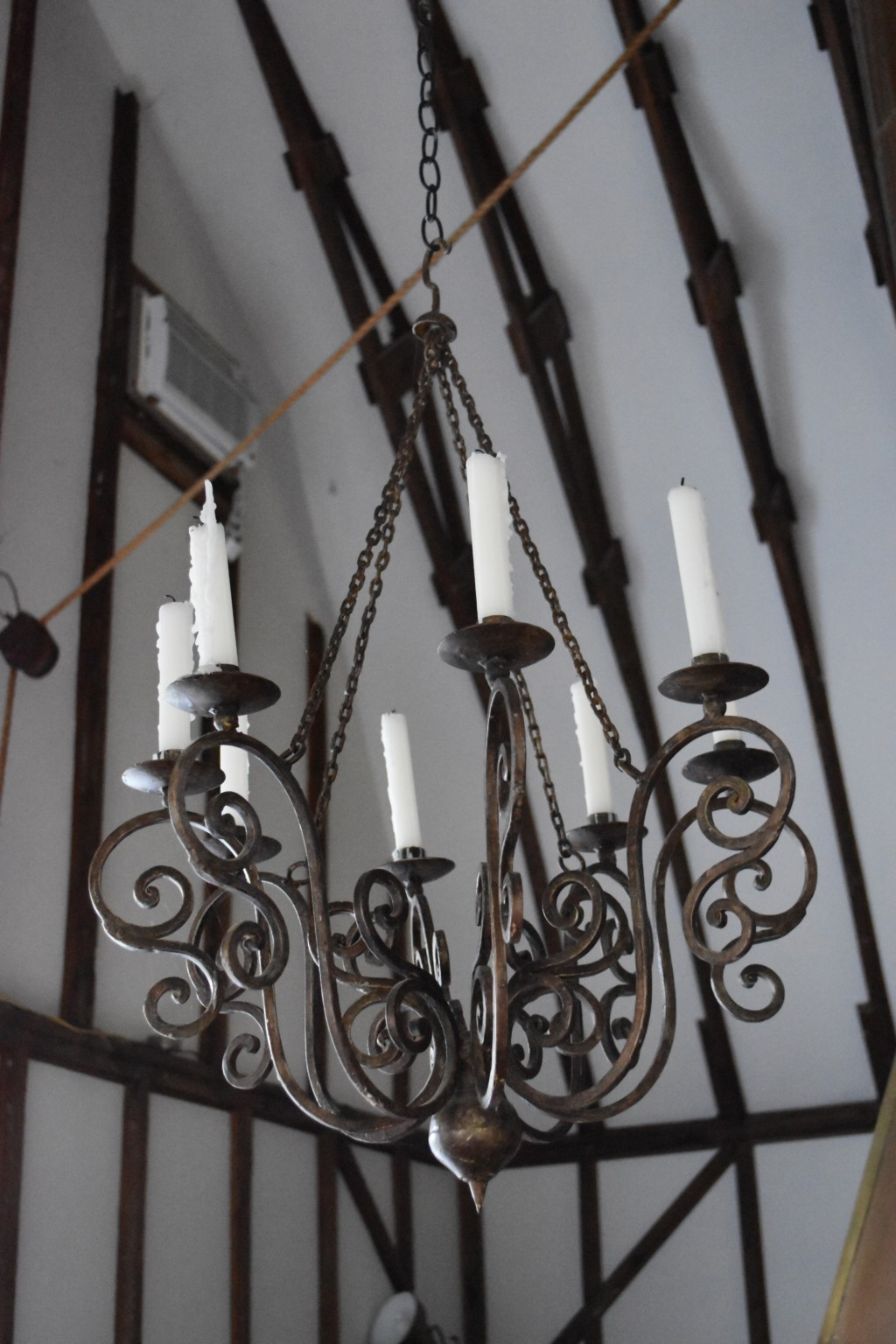 This pretty iron chandelier hangs by a heavy iron chain from the lofty ceiling. No electricity needed, these candles are old school. Love it.